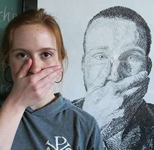 Art and graphic design major poses in front of her artwork.