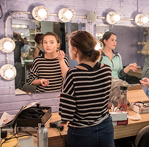 Theatre student putting on makeup for the University of Findlay's musical performance.