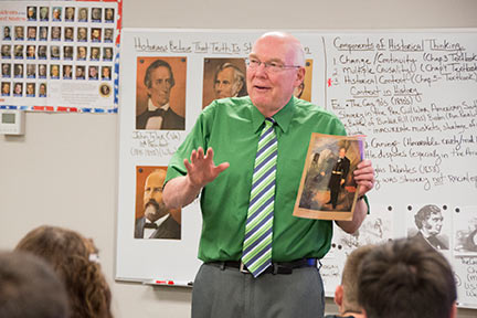 male teacher lectures while holding a book